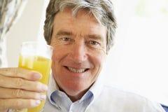 Homme aîné souriant et buvant du jus d'orange Image libre de droits