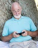 Homme aîné Texting Photographie stock libre de droits