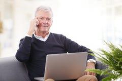 Homme aîné travaillant à la maison Photographie stock libre de droits