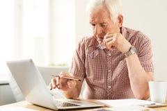 Homme aîné travaillant à la maison Photographie stock