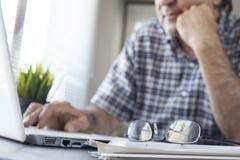 Homme aîné travaillant sur l'ordinateur Photos libres de droits