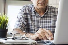 Homme aîné travaillant sur l'ordinateur Images libres de droits