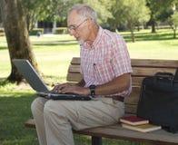 Homme aîné travaillant sur l'ordinateur portable à l'extérieur Image stock