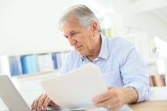 Homme aîné travaillant sur l'ordinateur portatif Images stock
