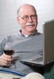 Homme aîné travaillant sur l'ordinateur portatif avec une glace de vin Photos stock