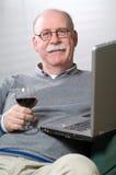 Homme aîné travaillant sur l'ordinateur portatif avec une glace de vin Photos libres de droits