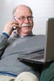 Homme aîné travaillant sur l'ordinateur portatif et appelant par le téléphone Image stock
