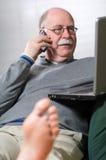 Homme aîné travaillant sur l'ordinateur portatif et appelant par le téléphone Images libres de droits