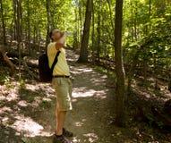 Homme aîné trimardant dans la forêt avec le sac à dos Photos stock