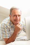 Homme aîné utilisant se reposer de détente d'ordinateur portatif sur le sofa Photos stock