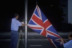 Homme abaissant le drapeau des Anglais Union Jack en Hong Kong Images libres de droits