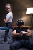 Homme absorbé par le jeu avec l'amie fâchée Photographie stock libre de droits