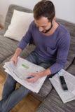 Homme accentuant des annonces dans un journal Images stock