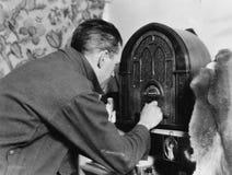Homme accordant la radio (toutes les personnes représentées ne sont pas plus long vivantes et aucun domaine n'existe Garanties de Photographie stock libre de droits