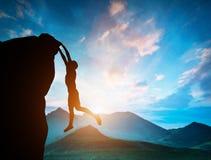 Homme accrochant au bord de la montagne au coucher du soleil Image libre de droits