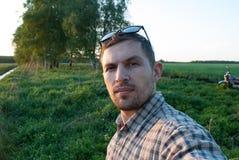 Homme actif en verres prenant un selfie dehors, photo stock