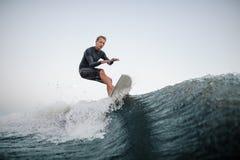 Homme actif wakesurfing sur le conseil en bas de la vague bleue dans la perspective du ciel clair image stock