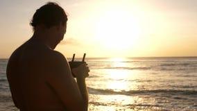 Homme actionnant un bourdon avec à télécommande Bourdon d'hélicoptère de Quadro volant au-dessus de l'océan de coucher du soleil  banque de vidéos