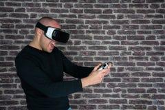 Homme adulte ayant l'amusement Jeu avec un casque de réalité virtuelle à la maison photo stock