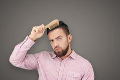 Homme adulte barbu avec le peigne en bois Photos stock