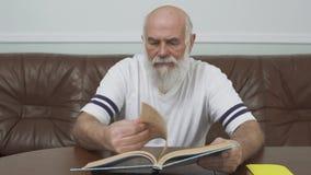 Homme adulte barbu réfléchi s'asseyant à la table en bois sur le sofa en cuir lisant le livre réserve vieux d'isolement par éduca clips vidéos