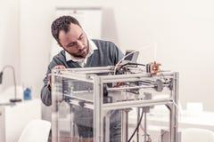 Homme adulte barbu travaillant avec l'imprimante 3D photo libre de droits