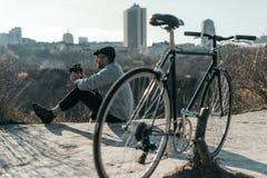 homme adulte bel avec la séance d'appareil-photo et de bicyclette de film de vintage photo stock