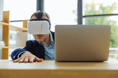 Homme adulte bel s'asseyant devant l'écran d'ordinateur portable photos stock