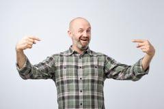 Homme adulte chauve mûr avec la barbe se tenant au-dessus du mur grunge gris semblant sûr avec le sourire sur le visage photographie stock libre de droits