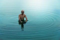 Homme adulte chauve situant en eau bleue de lac ou de mer d'été pour le fond de voyage et de nature de relaxation photo stock