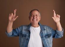 Homme adulte drôle croisant ses doigts tout en se tenant avec les yeux fermés image stock