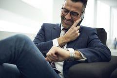 Homme adulte en veste et verres se réunissant tout en se reposant dans le bureau coworking avec la zone de wifi Image stock