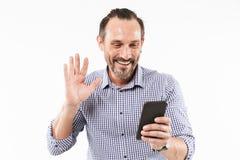 Homme adulte heureux parlant par le téléphone portable saluant des amis Photo libre de droits