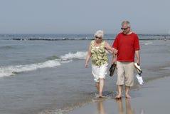 Homme adulte marchant avec le femme aîné sur la plage Photos libres de droits