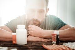 Homme adulte sombre triste regardant sa médecine photographie stock