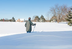 Homme adulte supérieur essayant de creuser la commande dans la neige Image stock