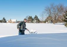 Homme adulte supérieur essayant de creuser la commande dans la neige Photographie stock libre de droits