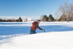 Homme adulte supérieur essayant de creuser la commande dans la neige Photo libre de droits