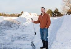 Homme adulte supérieur heureux après avoir creusé la commande dans la neige Image libre de droits