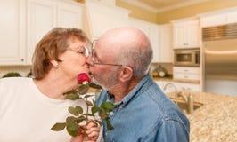Homme adulte supérieur heureux donnant Rose rouge à son épouse dans une cuisine Image libre de droits