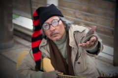 Homme adulte supérieur sans abri s'asseyant et priant en passage supérieur Photo libre de droits