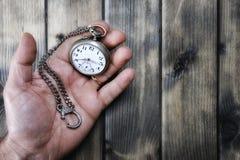 Homme adulte tenant une montre de poche antique dans sa main Images libres de droits