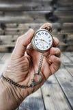 Homme adulte tenant une montre de poche antique dans sa main Photo stock
