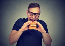 Homme affamé ayant le double hamburger images stock