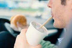Homme affamé conduisant sa voiture tout en buvant le soda le trafic photographie stock libre de droits
