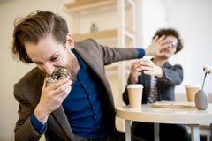 Homme affamé prenant le beignet hors de la femme image libre de droits