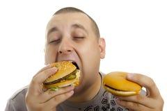 Homme affamé avec l'hamburger. Photos libres de droits