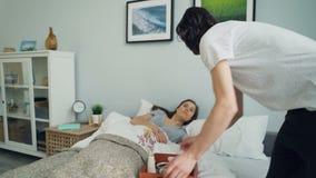 Homme affectueux apportant le petit déjeuner dans le lit pour le sourire de baiser d'amie de sommeil banque de vidéos