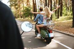Homme affectueux de couples sur le scooter avec l'amie dehors Image stock