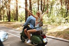 Homme affectueux de couples sur le scooter avec l'amie dehors Photos stock